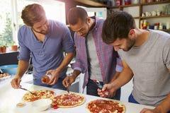 Drei männliche Freunde, die zusammen Pizza in der Küche machen Stockfotos