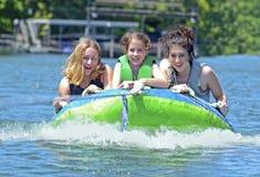 Drei Mädchen auf einem Rohr Stockbilder