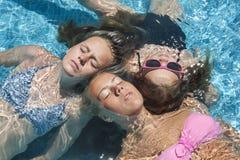Drei Mädchen, die im Pool sich entspannen Stockbild