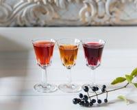 Drei mehrfarbige Alkohole auf weißem hölzernem Hintergrund der Weinlese Ð-¡ opy Raum lizenzfreies stockbild