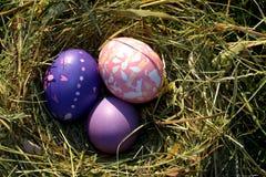 Drei mehrfarbige Eier im Heu stockbild