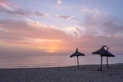 Drei mit Stroh gedeckte Strandschirme auf einsamem Strand während des Wintersonnenuntergangs lizenzfreie stockfotos