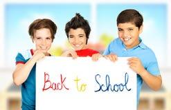 Drei Mitschülerjungen, die im Klassenzimmer spielen Lizenzfreie Stockfotos