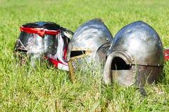 Drei mittelalterliche Ritter ` s Sturzhelme auf dem Gras Lizenzfreie Stockbilder
