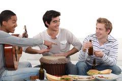 Drei männliche Freunde, die Instrumente spielen Stockbild