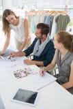 Drei Modedesigner, die Designe besprechen Lizenzfreie Stockfotografie