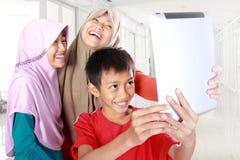Drei moslemische Kinder, die Tablet-Computer spielen Stockbild