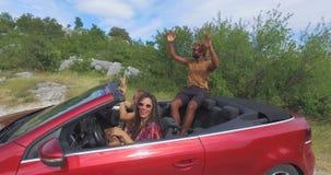 Drei multi ethnische Freunde, die im roten Kabriolett partying sind, parkten auf Seite der Straße stock video footage