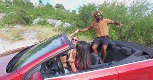 Drei multi ethnische Freunde, die im roten Kabriolett partying sind, parkten auf Seite der Straße stock footage