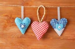 Drei nähten die roten Herzen, die vom Stoff gemacht wurden, der auf einer Wäscheleine hängt Stockbild