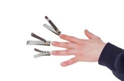 Drei Nagelscherer gegenüber von den Fingern einer männlichen Hand Stockbild