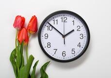 Drei natürliche Tulpenblumen und -uhr auf weißem Hintergrund - Zeit-, Liebes- und Feiertagskonzept Stockfotos
