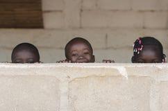 Drei nette afrikanische Kinder, die draußen Peekaboo spielen Stockfotos