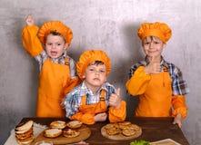 Drei nette Jungen in den Kost?mk?chen teilgenommen an dem Kochen von selbst gemachten Burgern stockfotos