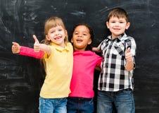 Drei nette Kinder, die oben zusammen mit Daumen stehen Lizenzfreie Stockbilder