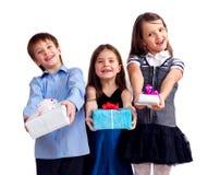 Drei nette Kinder gibt Geschenke Stockfoto