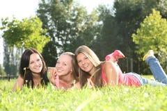 Drei nette Mädchen, die im Gras aufwerfen Lizenzfreie Stockbilder