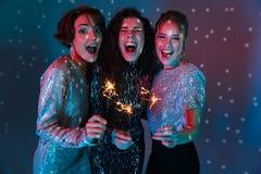 Drei nette Schönheiten, die helle Kleidung tragen stockfotografie