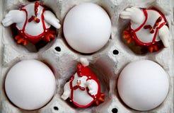 Drei Ostern-Hahndekorationen und rohe Eier stockfoto