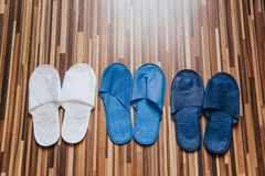Drei Paare der farbigen Pantoffel sind auf dem Boden im Hotelzimmer stockfotos