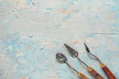 Drei Palettenmesser auf Künstlersegeltuch mit Ölfarbe Stockfoto