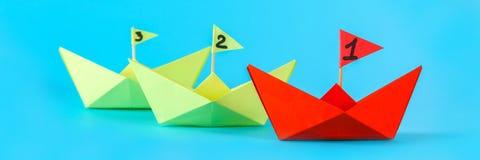 Drei Papierschiffe konkurrieren, wem schneller schwimmt Rot gewinnt das Schiff lizenzfreies stockbild