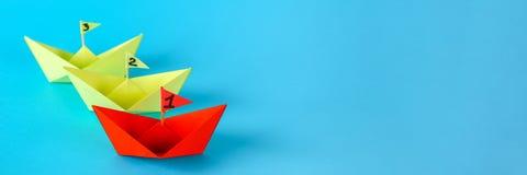 Drei Papierschiffe konkurrieren, wem schneller schwimmt Rot gewinnt das Schiff lizenzfreie stockfotos