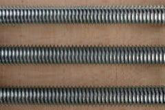 Drei parallele Schrauben am hölzernen Hintergrund Stockbilder