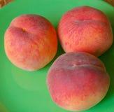 Drei Pfirsiche auf einer grünen Platte Stockfotos