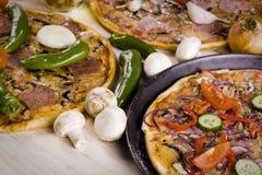 Drei Pizzas mit Soße und Teilen Stockbild
