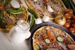 Drei Pizzas mit Soße und Teilen Stockbilder