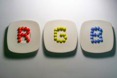 Drei Platten mit bunten Süßigkeiten von Schokoladen mit RGB-Farben Stockfotos