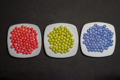 Drei Platten mit bunten Süßigkeiten von Schokoladen mit RGB-Farben Lizenzfreie Stockfotografie