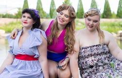 Drei Plusgrößenmodelle sitzen auf dem See Stockfotos