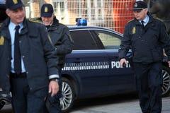 Drei Polizeimänner und -auto in der Aktion stockbilder