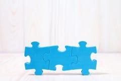 Drei Puzzlespielstücke auf weißem hölzernem Hintergrund Stockfoto