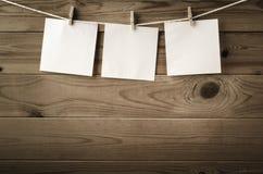 Drei quadratische Anzeigen-Anmerkungen verdübelt auf Wäscheleine Stockfoto