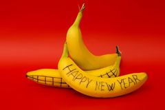Drei reife Bananen mit Zeichnungen und dem Aufschrift ` guten Rutsch ins Neue Jahr ` Stockfotografie