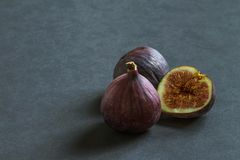 Drei reife Feigenfrüchte auf einem grauen Hintergrund lizenzfreie stockbilder