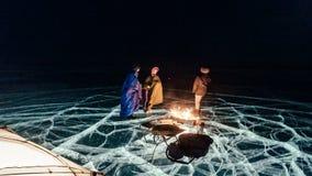 Drei Reisende durch das Feuerrecht auf dem Eis nachts Campingplatzeis Das Zelt steht nahe bei dem Feuer Leute sind stock video