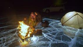 Drei Reisende durch Feuerrecht auf Eis nachts Campingplatz auf Eis Zelt steht nahe bei Feuer See Baikal In der Nähe gibt es stock video footage