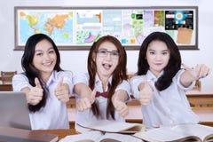 Drei reizende Studenten, die sich Daumen zeigen Stockfotos
