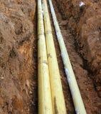Drei Rohre im Graben im Boden Stockbild