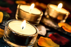 Drei romantische Kerzen-Lichter auf Schiefer mit Rose Petals And Leafs lizenzfreie stockfotografie