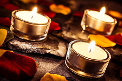 Drei romantischer Valentine Tealights On Slate With Rose Petals And Leafs Lizenzfreies Stockfoto