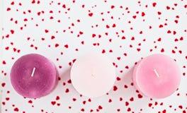 Drei rosa Kerzen auf einem roten herzigen Hintergrund Stockbild