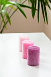 Drei rosa ombre duftende Kerzen auf weißer Tabelle lizenzfreie stockfotografie