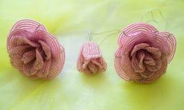 Drei Rosen gemacht von den Perlen, vom Rosa, von zwei Knospen und von einer Blume Auf einem gelben unscharfen Hintergrund lizenzfreie stockfotos