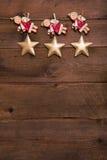 Drei rot und goldene Weihnachtsengel auf altem hölzernem Hintergrund f Stockbild