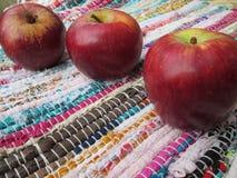 Drei rote Äpfel auf einer gesponnenen Matte stockfotografie
